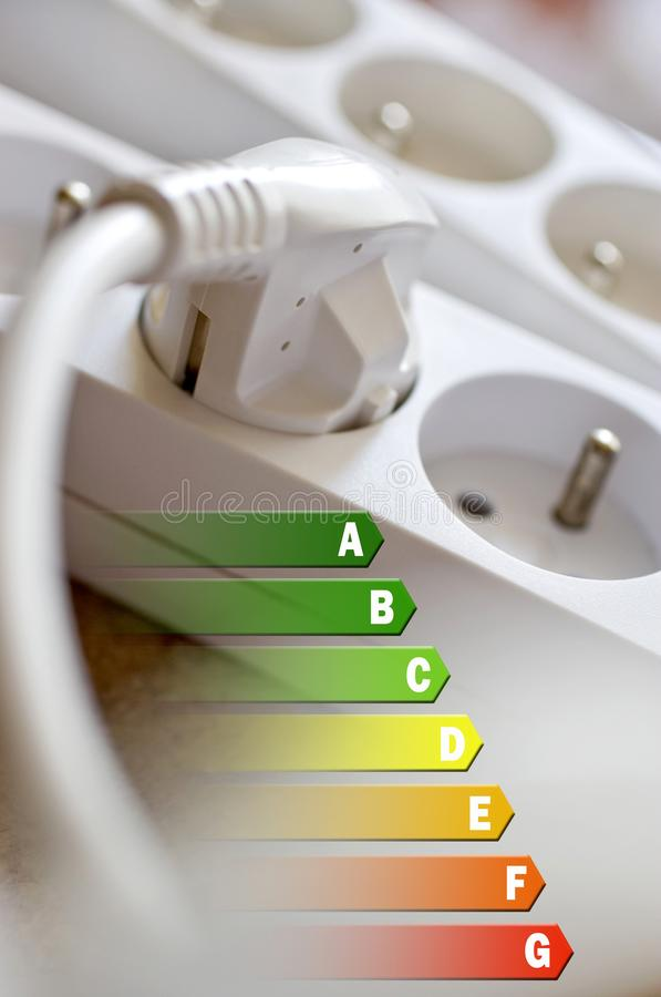 Energy efficiency label for house / electricity and money savings - plug in a socket. White royalty free stock image