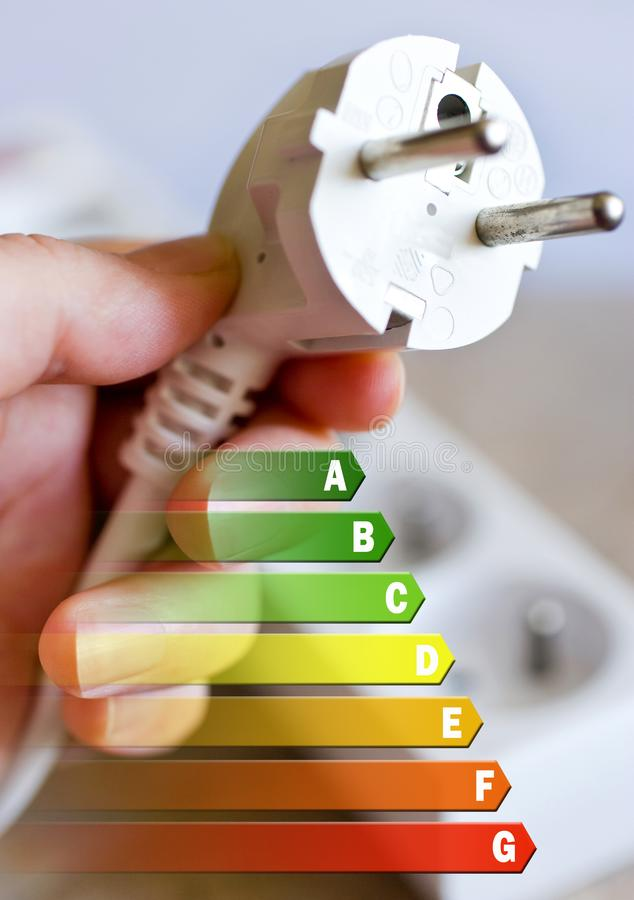 Energy efficiency label for house / electricity and money savings - plug in a hand royalty free stock images