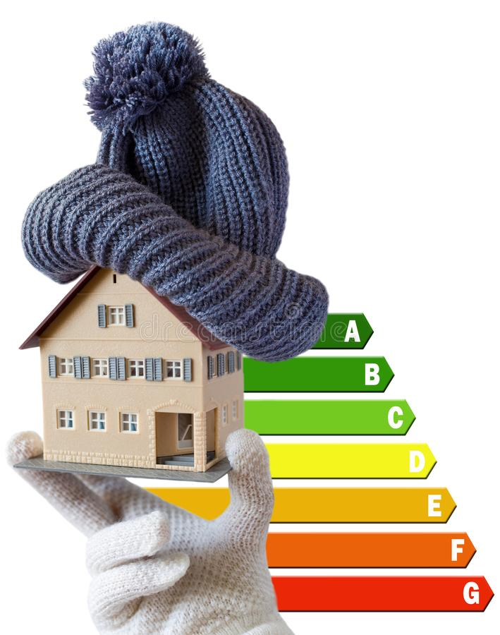Energy efficiency label for house / heating and money savings - model of a house with cap in a hand in gloves royalty free stock photo