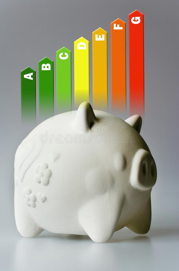 Energy efficiency label for house / heating and money savings - piggy bank on the grey background. Energy efficiency label for a family house / heating and money stock images