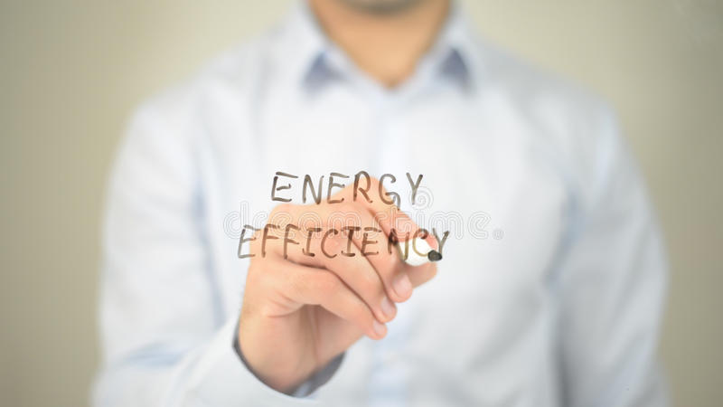 Energy Efficiency, man writing on transparent screen royalty free stock image