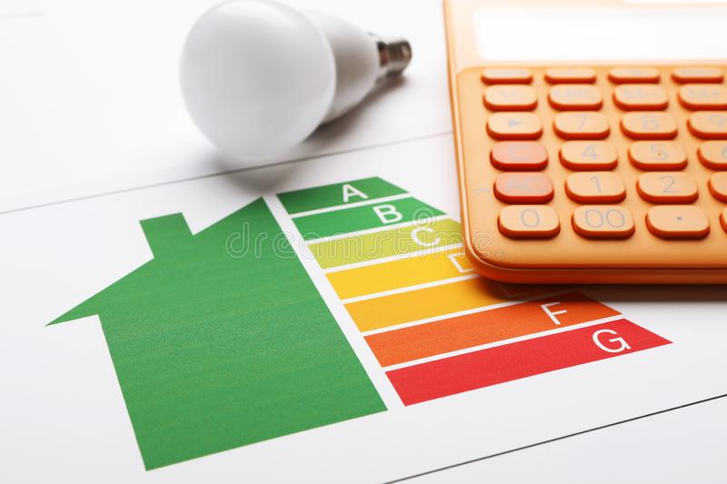 Energy efficiency rating chart, LED light bulb and calculator on white background royalty free stock photo
