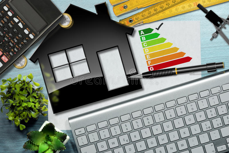 Energy Efficiency Rating with House Model. Energy efficiency rating graph on a desk with a house model, calculator, folding ruler, drawing compass, pencil and a stock photo