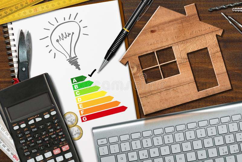 Energy Efficiency Rating - Wooden House Model. Energy efficiency rating graph on a desk with a wooden house model, calculator, folding ruler, light bulb and a stock photography