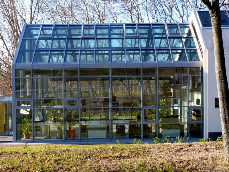 Energy efficient glass house in rural setting in winter time. Energy efficient glass house with aluminum mullion frame in rural setting in winter time with bare royalty free stock photography