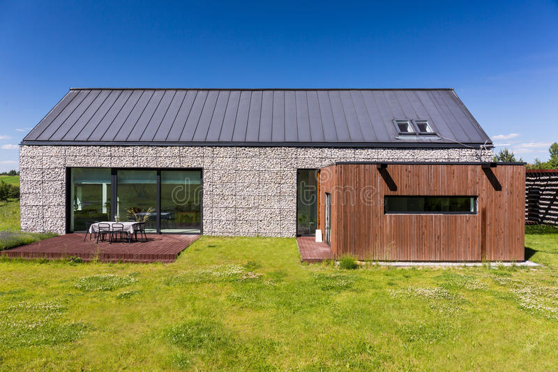 Energy-efficient house covered with pebbles. Simple shape of an energy-efficient house covered with pebbles, with wooden garage and a terrace deck stock image