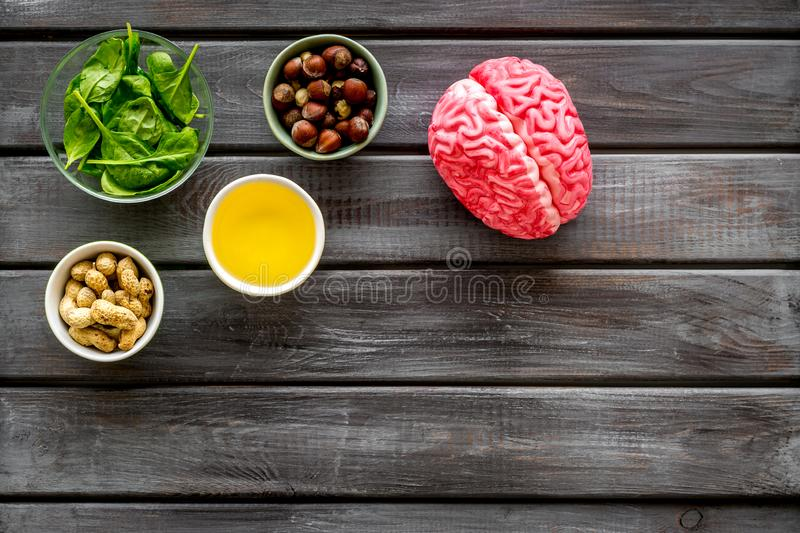 Energy food for brain work with peanut, hazelnut, seed-oil, spinage on wooden background top view space for text. Health care. Energy food for brain work with stock photos
