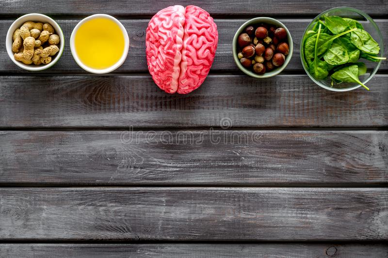 Energy food for brain work with peanut, hazelnut, seed-oil, spinage on wooden background top view space for text. Health care. Energy food for brain work with royalty free stock image