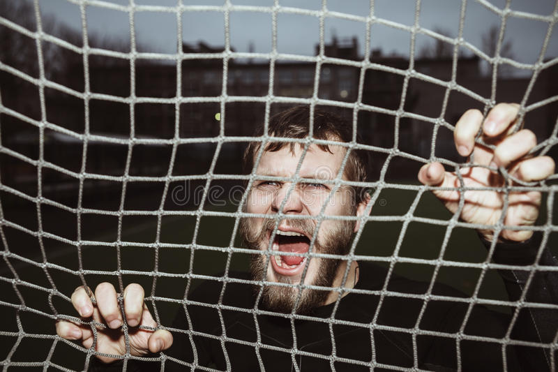 Energy furious bearded athlete screaming holding net. Outdoor royalty free stock images