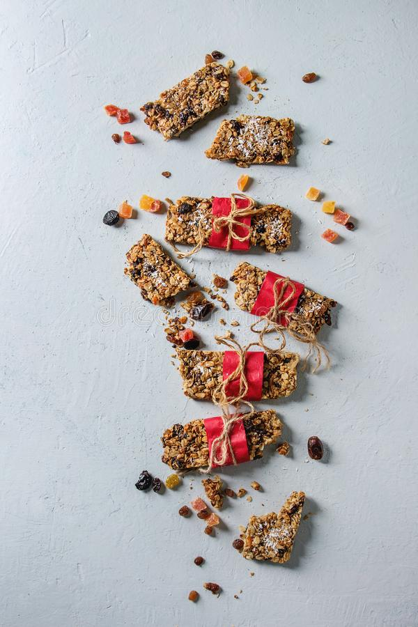Energy granola bars. Homemade energy oats granola bars with dried fruits and nuts whole and broken wrapped in red paper over white texture background. Healthy royalty free stock photography