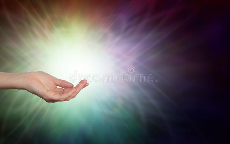Energy healer with open hand and energy formation. Female hands sensing life force energy with open palm inside a multicoloured ball of light with copy space royalty free stock image