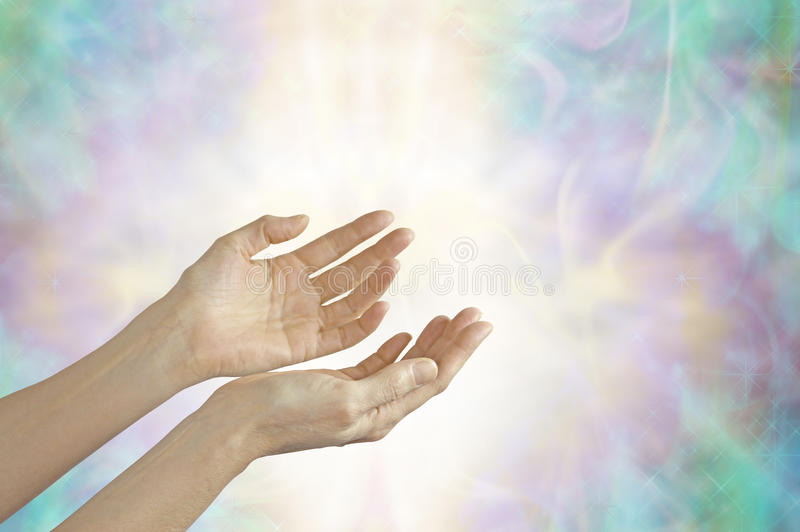 Energy healer with open hands. Female hands sensing life force energy with open palms on a beautiful pastel misty energy formation background royalty free stock photography