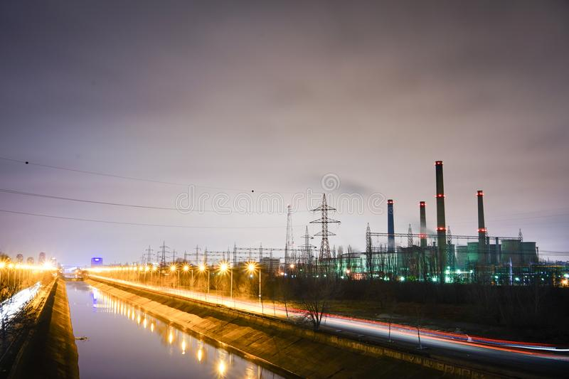 Energy and power to the city. Grey image, red and yellow light lines. Power plant, urban periphery High tension poles, night scene, metallic structures, energy stock photography