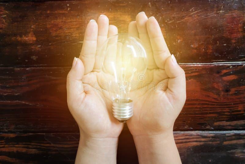 Energy-saving concept Een gloeilamp op de vrouwen` s hand die wordt geplaatst stock fotografie