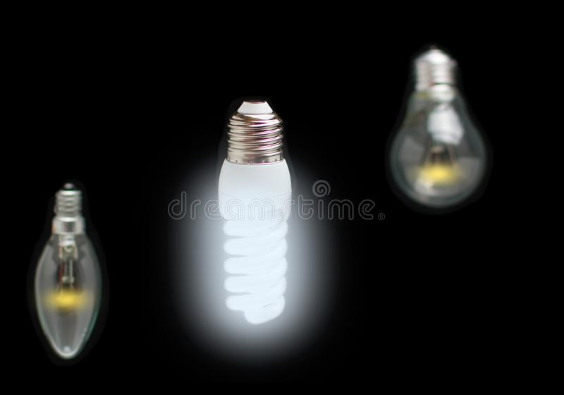 Energy-saving concept of innovation of bright fluorescent lamps, green technology and old dim incandescent bulbs. royalty free stock image