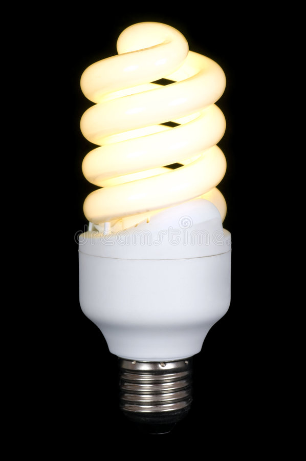 Energy saving fluorescent lamp. Lighting compact energy saving spiral fluorescent lamp isolated on black background stock photography