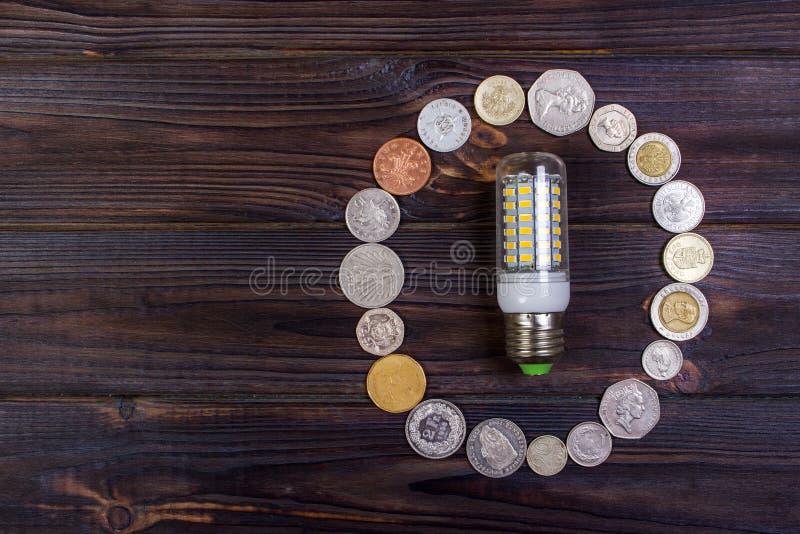 Energy saving fluorescent lamp on money background, Eco energy saving light bulb, comparison of energy saving lamps and incandesce royalty free stock image