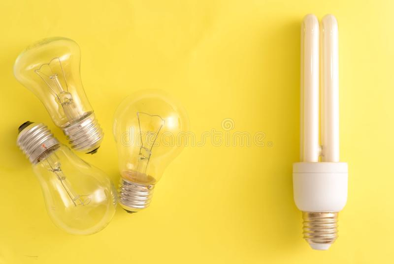 Energy-saving lamp vs. incandescent lamps. The concept of energy saving . On a yellow background.One energy-saving bulb corresponds to three incandescent bulbs royalty free stock photo