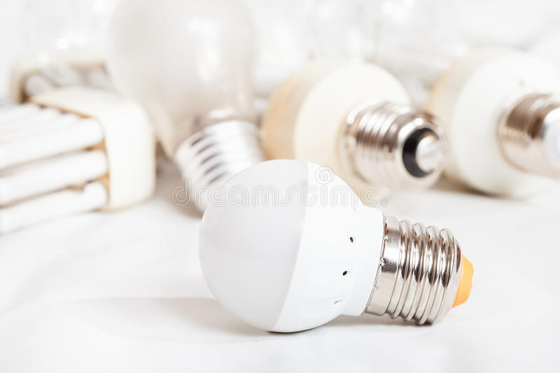 Energy saving LED lamp and several old light bulbs stock photography