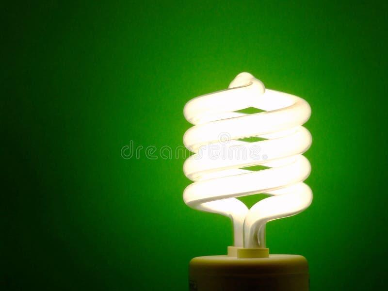 Energy-Saving Light Bulb. A compact fluorescent light bulb illuminating a green background stock photo