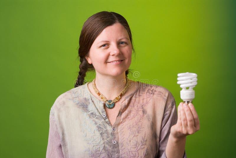 Energy saving light bulb. An environmentalist holds a compact fluorescent light bulb stock image