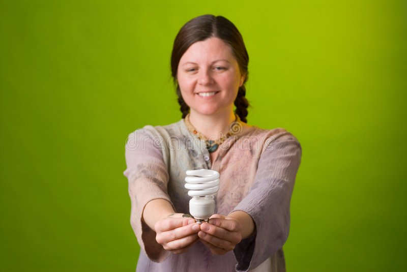 Energy saving light bulb. An environmentalist holds a compact fluorescent light bulb royalty free stock images
