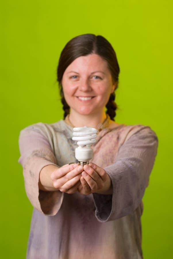 Energy saving light bulb. An environmentalist holds a compact fluorescent light bulb royalty free stock photography