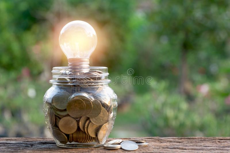 Energy saving light bulb and coins in glass jar on nature background. Saving, accounting and financial concept. royalty free stock photos