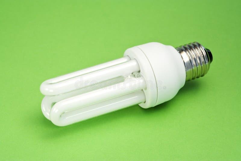 Energy saving light bulb on green surface stock photography