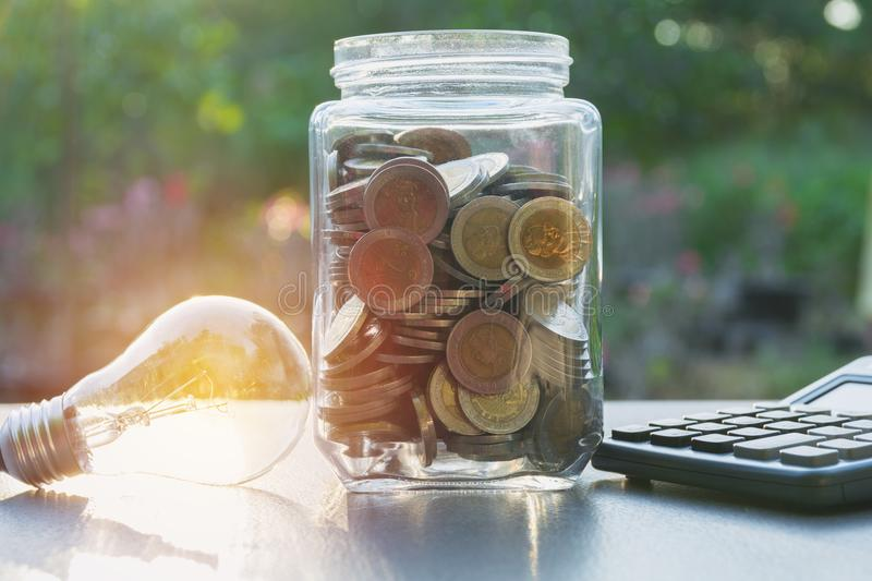 Energy saving light bulb with money in the jar and calculator royalty free stock photography