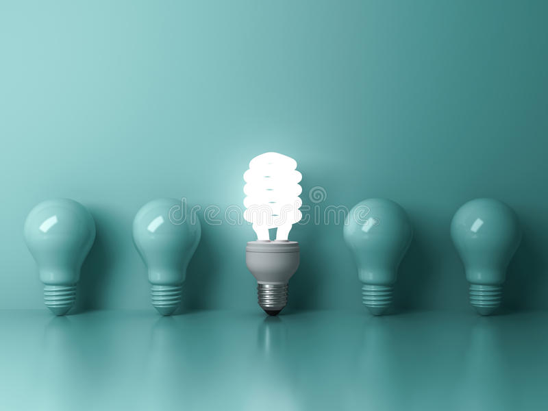 Energy saving light bulb , one glowing compact fluorescent lightbulb standing out from unlit incandescent bulbs on green stock illustration