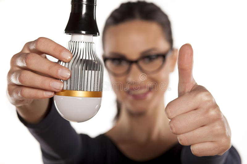 Energy saving lighting. Young woman holding LED bulb and showing thumb up royalty free stock photos