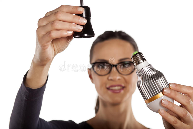 Energy saving lighting. Young woman mounting LED light bulb in the socket stock photography