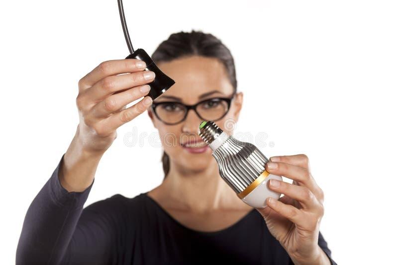 Energy saving lighting. Young woman mounting LED light bulb in the socket stock photo