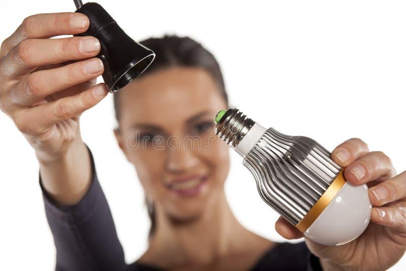 Energy saving lighting. Young woman mounting LED light bulb in the socket stock image