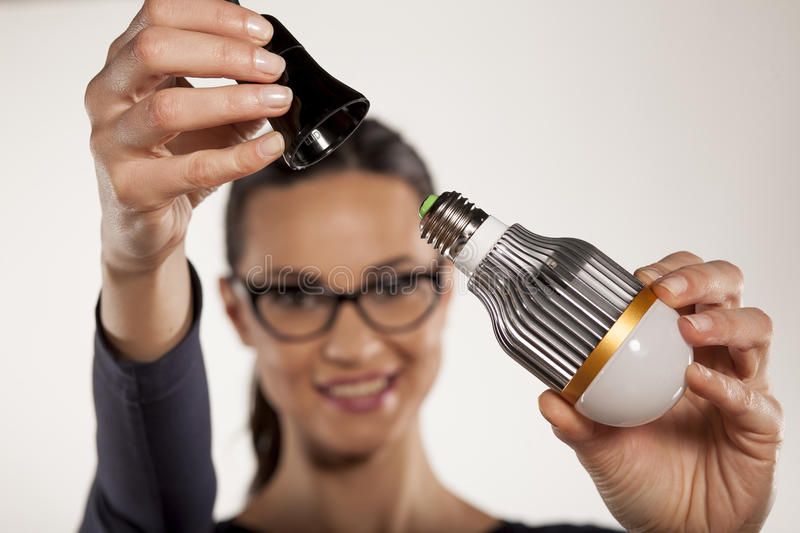 Energy saving lighting. Young woman mounting LED light bulb in the socket royalty free stock photography