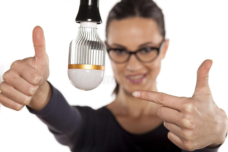 Energy saving lighting. Young woman pointing at LED bulb and showing thumbs up royalty free stock photo