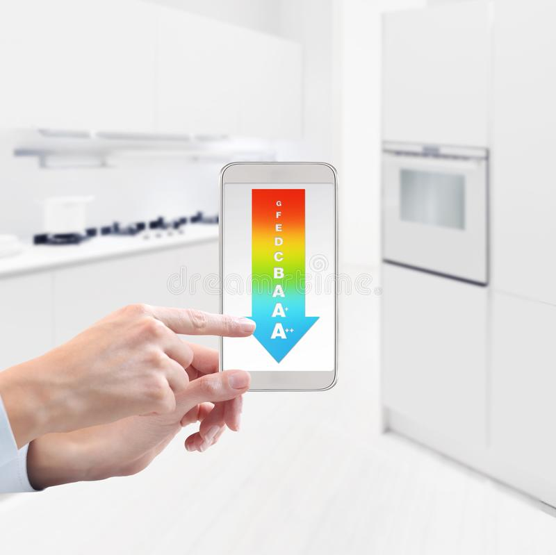 energy saving and smart home automation control concept hand touch screen of cell phone with efficiency class symbol on blurred k royalty free stock images