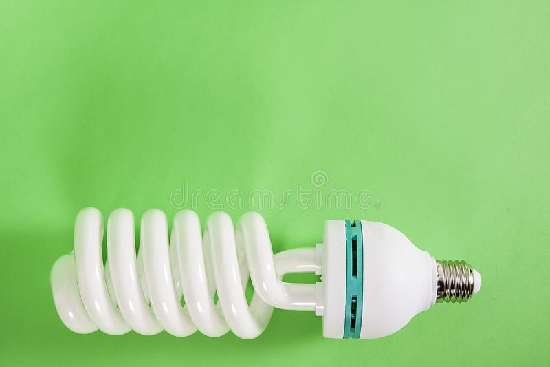 Energy saving spiral electric bulb on green background stock photo