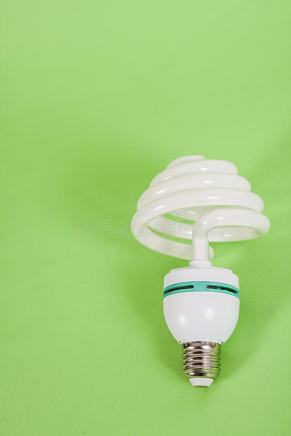 Energy saving spiral electric bulb on green background royalty free stock photos