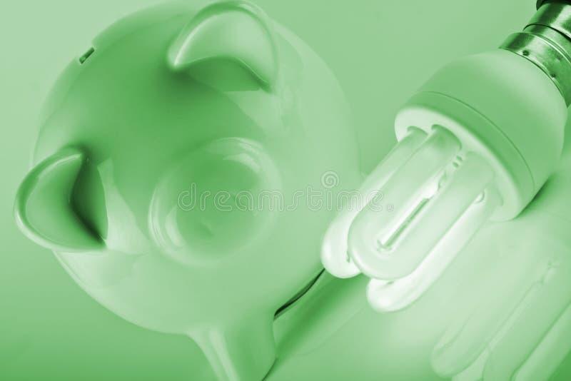 Energy savings. Piggybank with energy savings compact fluorescent lightbulb royalty free stock photo