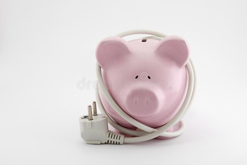 Energy Savings concept. Piggy bank with power plug stock photos