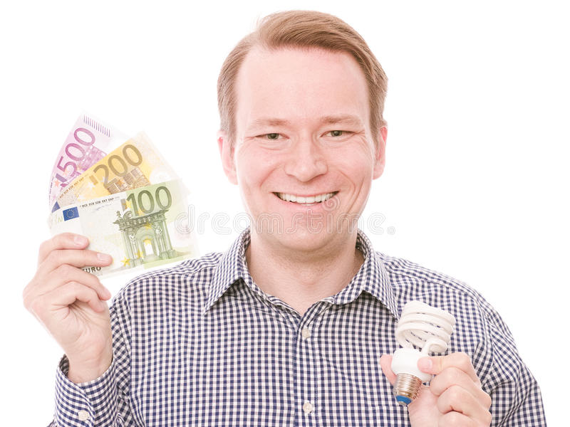 Energy savings. Young smiling man holding an energy saving lightbulb and some euro banknotes - isolated on white royalty free stock image