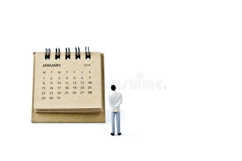 enero Haga calendarios la hoja y al hombre plástico miniatura en el backg blanco fotos de archivo