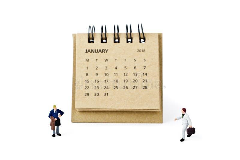 enero Haga calendarios la hoja y a los hombres de negocios plásticos miniatura en whi imagenes de archivo