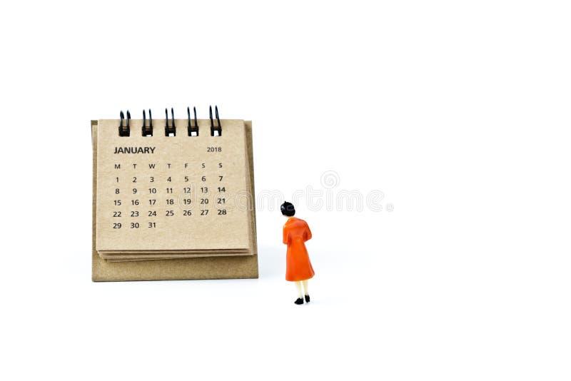enero Haga calendarios la hoja y a la mujer plástica miniatura en el CCB blanco foto de archivo