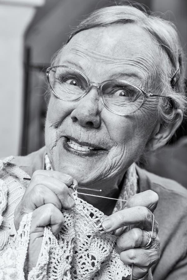 Enfaldig gammal dam med virkning royaltyfri fotografi