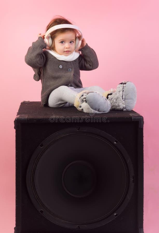 enfance et bonheur l'enfant écoutent musique avec le casque et le mp3 au téléphone Petite fille heureuse Haut-parleur sonore Peti image libre de droits