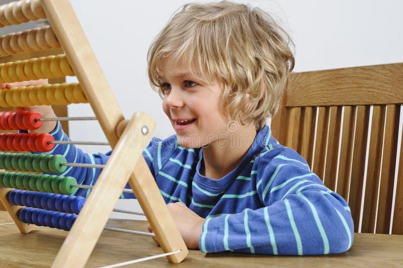 Enfant à l'aide d'un abaque image stock