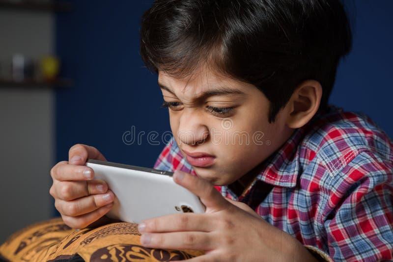 Enfant à l'aide d'un Smart-téléphone avec l'expression drôle images libres de droits